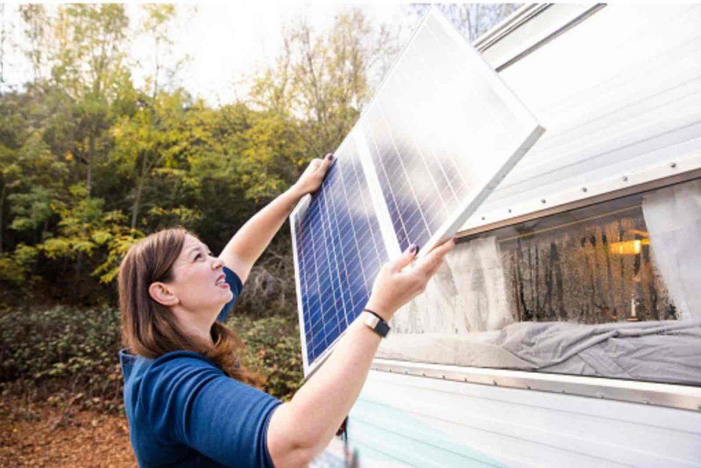 Woman installing Solar Panel on RV
